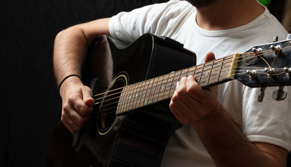 Young man playing guitar, close up view, dark background