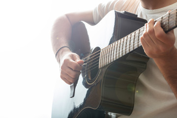 Young man playing guitar, close up view, white background