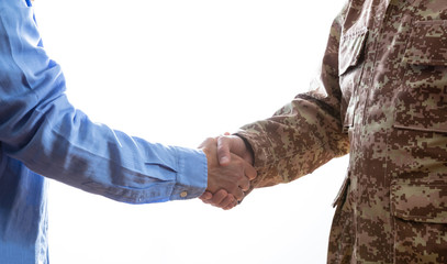 Military and civilian shaking hands standing on white background