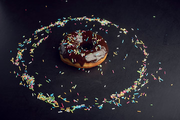 Chocolate donut in circle of colourful sprinkles, tasty dessert
