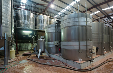 Stainless cisterns with fermenting wine in fabric
