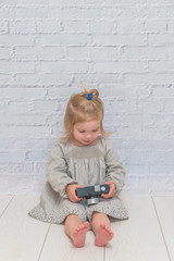 girl, child with vintage camera on white brick wall background