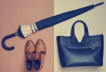 Autumn collection of women's accessories and shoes. Demi-season boots, an umbrella, a leather bag on a creamy brown paper background. Top view.
