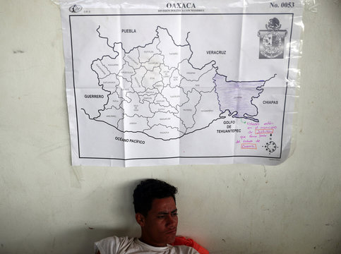 A migrant, part of a caravan of thousands traveling from Central America en route to the United States, sits below a map of the state of Oaxaca whilst he rests in a makeshift camp in Juchitan