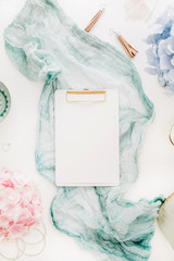 Home office desk with clipboard with copy space, turquoise blanket, colorful pastel hydrangea flower bouquet, woman fashion accessories on white background. Flat lay, top view workspace mockup.