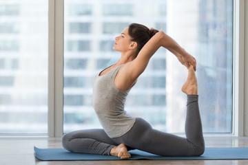 Young sporty woman doing yoga, One Legged King Pigeon exercise, Eka Pada Rajakapotasana pose, working out, wearing sportswear, grey pants and top, indoor full length, yoga studio. Wellness concept