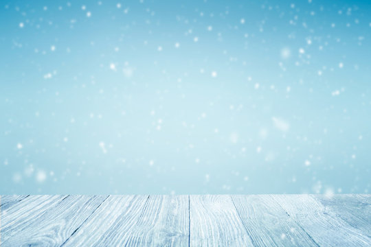Winter background, falling snow over wooden deck