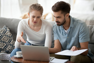 Frustrated married couple has financial problems wife and husband received bad news from bank about debt high taxes. Millennial woman and man reading mail on laptop holding paper letter domestic bill