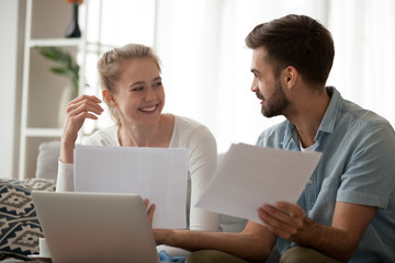 Happy young married couple sitting on couch at home using computer holding paper letter reading received good news about refund or income. Smiling excited wife and husband discussing planning budget