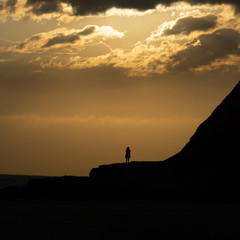 silhouette of woman during sunset next to the sea