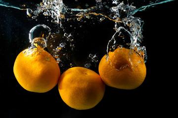 Three ripe mandarine in water splash on black
