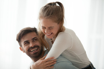 Happy millennial young man and woman hugging embracing indoors. Portrait of excited smiling husband and wife piggyback ride sincere laughing together at home. Dating and romantic relationship concept