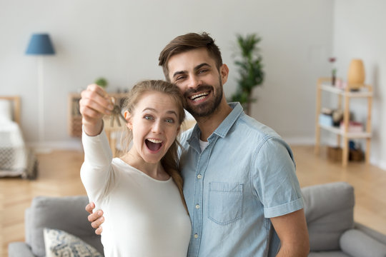 Smiling married couple in love standing hugging in living room at new modern house looking at camera. Excited wife holding keys from their new dwelling. Happy family, moving real estate owners concept
