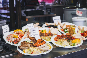 Delicious plates with a variety of grilled fish and seafood with mashed potatoes served with salad and a lemon wedges. Street Food ready to eat with price tag at Bergen Fish Market, Norway