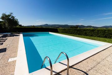 Leerer Swimmingpool vor blauem Himmel in der Toscana
