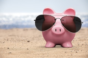 Summer piggy bank with sunglasses on the