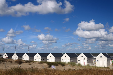 Tiny Beach Houses.Row of 8 white small wooden houses on an empty beach. In the background the horizon of the ocean and a beautiful blue sky full of white clouds, like whipped cream.