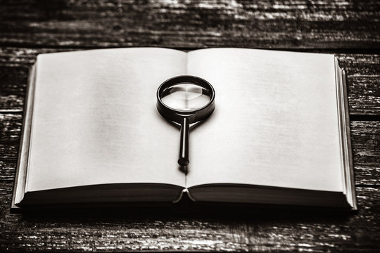 Retro magnifier and opened book on wooden table.