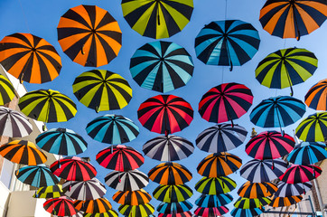 Colorful umbrellas background. Colorful umbrellas in the sunny sky. Street decoration.