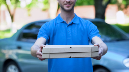 Friendly delivery man giving pizza box, food order online, restaurant service
