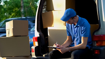 Delivery man filling transportation documents, sitting near van trunk, duties