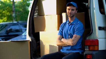 Deliveryman smiling into camera, sitting in van, fast parcels transportation