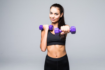 Young attractive woman in sport clothes with beautiful smile holding weight dumbbell doing fitness workout isolated on white background. Healthy lifestyle concept
