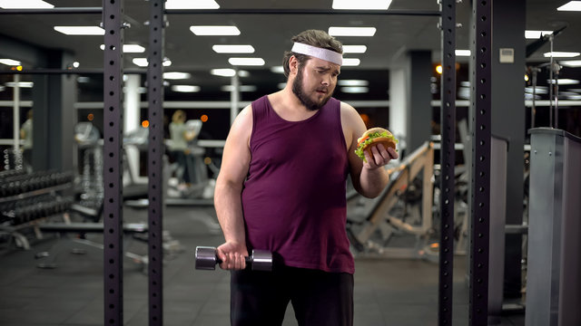 Overweight man holding burger and dumbbell in hands, life decision, motivation