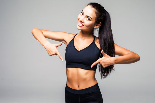 Cheerful young healthy woman in sportswear pointing on her belly isolated on gray background