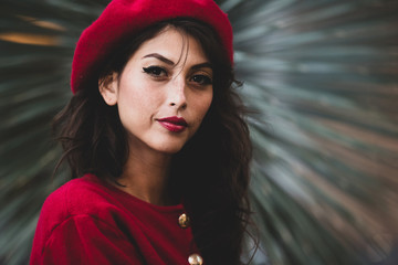 Pretty and confident young woman displaying French fashion in the form or a red beret Wall mural