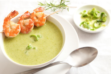 king prawn skewer on green vegetable cream soup, white tableware
