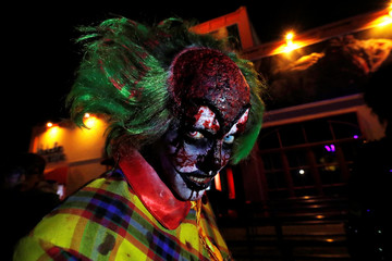 A participant in costume and make-up poses for a photo during a Halloween parade at Walibi park in Wavre