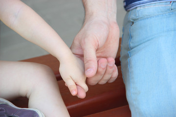 Father holding daughter's hand. children's hand holds the male hand by the finger , sitting on the bench