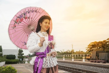 The pretty Thai lady in Middle Thai classical traditional dress suit standing and hold paper umbrella is posing at railway station.