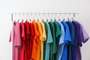Rack with bright clothes on white background. Rainbow colors