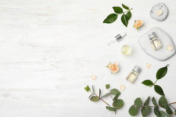 Essential oil, ingredients and space for text on wooden background, flat lay