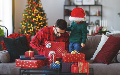 family   father and child son open presents on Christmas morning