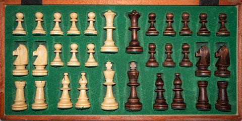 wooden chess pieces (white / black) are neatly folded in a box with a green background
