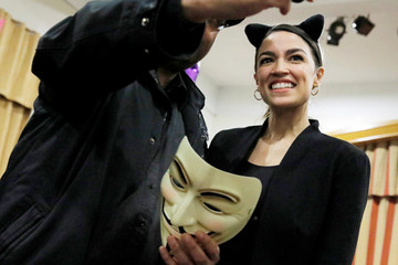"""Democratic Congressional candidate Ocasio-Cortez poses for a photo as she attends the """"Halloween with Alexandria"""" event at St Paul's Evangelical Lutheran Church in the Bronx"""
