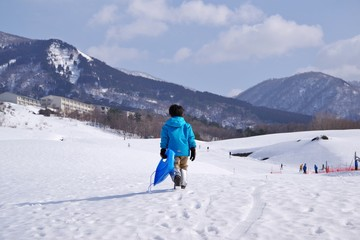 スキー場でそり遊びをするキッズ