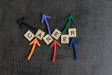 Random career path opportunities concept by colorful wooden alphabets building word CAREER with multi directional arrow on dark chalkboard background wall