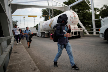 A man in a caravan of migrants from El Salvador en route to the United States, crosses the Arce bridge at the El Salvador-Guatemala border in San Francisco Menendez, El Salvador