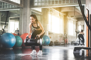 Strong woman in sportswear does the exercises weight training at gym