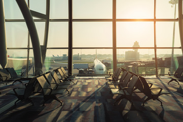 Empty chairs in the departure hall at airport with airplane taking off at sunset. Travel and transportation in airport concepts.
