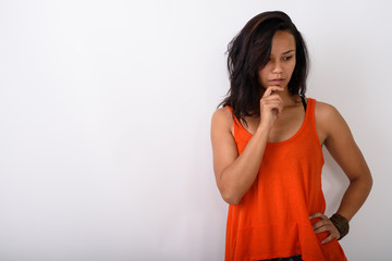 Studio shot of young Asian woman thinking while looking down aga