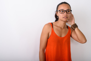 Studio shot of young Asian woman thinking while listening and we