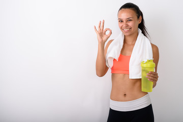 Young happy Asian fitness woman smiling while giving ok sign