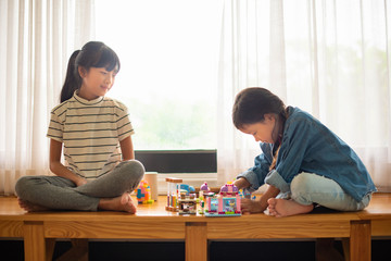Two sisters playing on the sofa in the home, Freedom and carefree, Happy childhood, happy family friendship between siblings, family leisure time in living room.