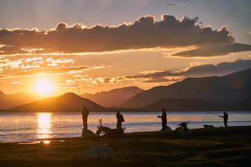 Mongolian dwellers are fishing on Hoton-nuur lake in sunset time