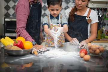 Closeup of  hand son wears apron,sprinkle with flour as prepares delicious pizza, going to make surprise for family and treat with tasty pastry, Baking concept.